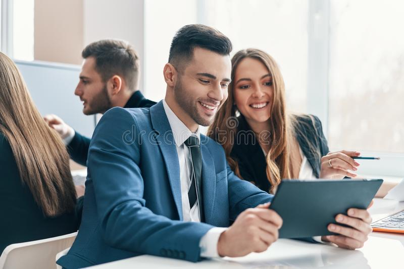 Smiling successful business people discussing ideas using digital tablet in office royalty free stock photos