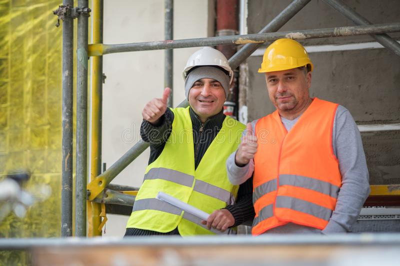 Smiling and successful construction workers posing showing thumbs up gesture stock photography