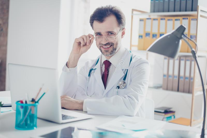 Smiling successful doctor fixing his glasses, sitting at the desktop of his workplace, which is modern and light stock image