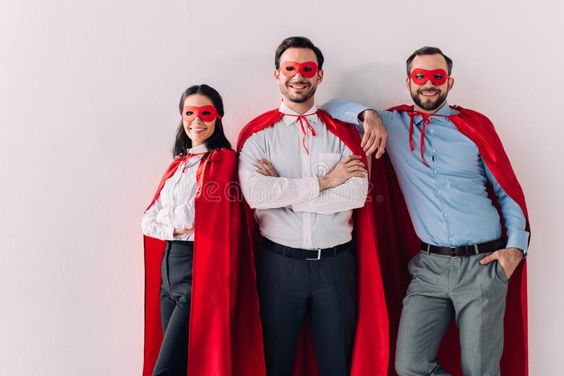 smiling super businesspeople in masks and capes looking at camera royalty free stock image