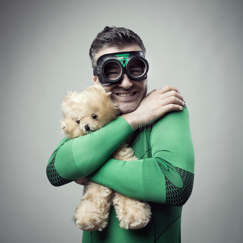 Smiling superhero cuddling a teddy bear. Smiling cheerful superhero holding a cute teddy bear stock photos