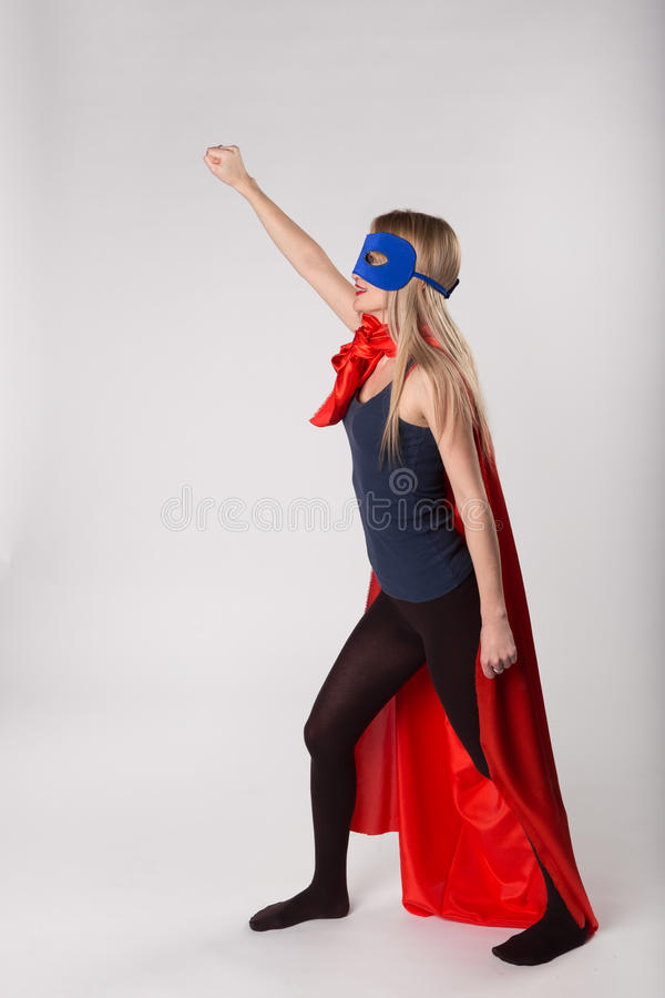 Smiling superhero female raised her hand up. Young woman posing in studio stock image