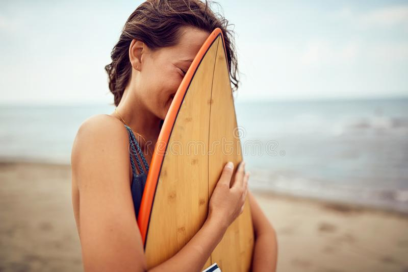 Surfer woman posing with her surfboard on the beach. Smiling surfer woman posing with her surfboard on the beach royalty free stock photography