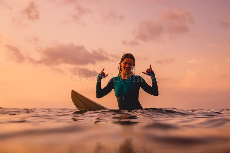 Smiling surfer woman sit on a surfboard in ocean. Surfing at sunset royalty free stock photo