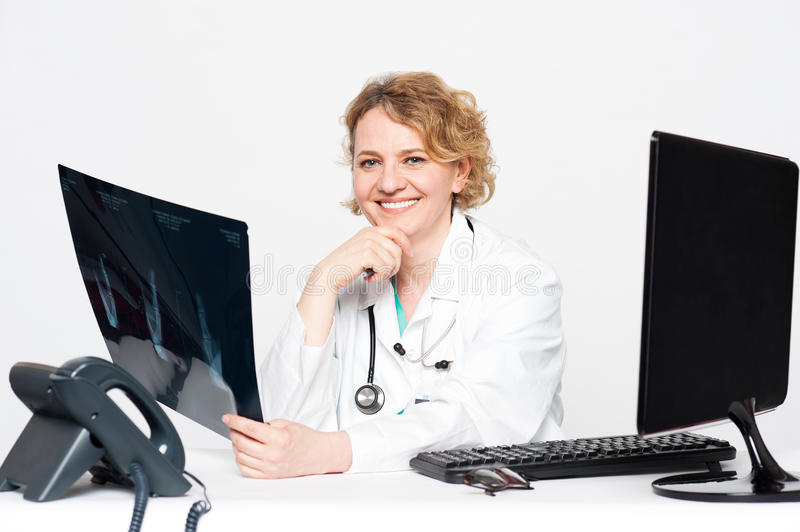 Smiling surgeon holding x-ray report. Sitting in her clinic stock photos