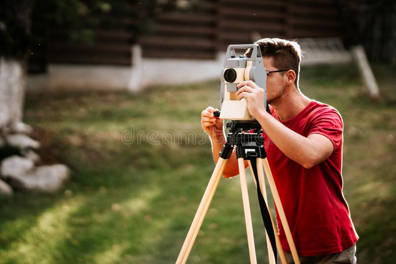 Smiling surveyor working with total station with coordinates, cartography industry details. Portrait of smiling surveyor working with total station with royalty free stock images