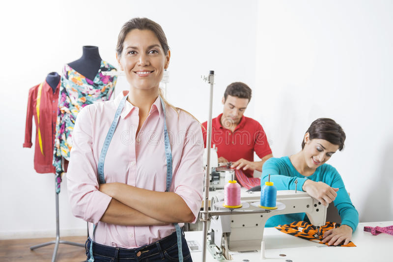 Smiling Tailor With Arms Crossed Standing In Sewing Factory stock photography
