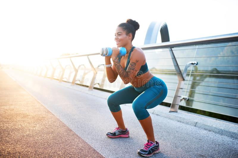 Smiling tattooed woman doing sit ups with barbells in arms. Barbells in arms. Smiling tattooed woman doing sit ups with barbells in arms on nice summer day stock photography