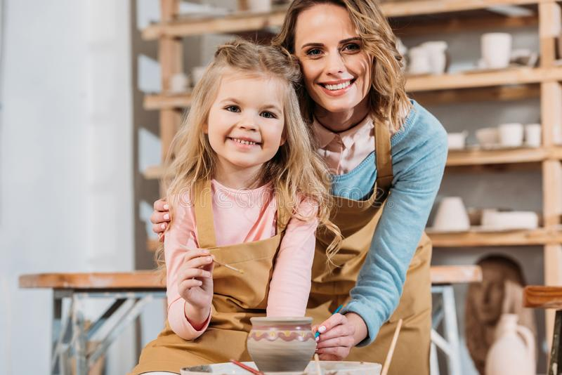 smiling teacher and child painting ceramic pot together stock photos