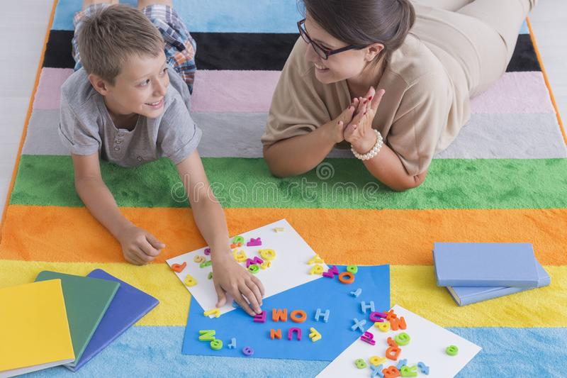 Smiling teacher and child. Lie on a colorful carpet and play during school activities stock photography