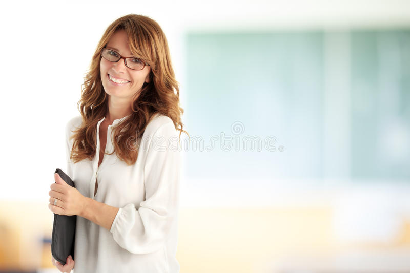 Smiling teacher in front of the blackboard royalty free stock photography