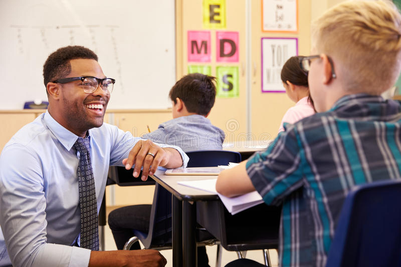 Smiling teacher kneeling beside elementary school pupil�s desk royalty free stock photography