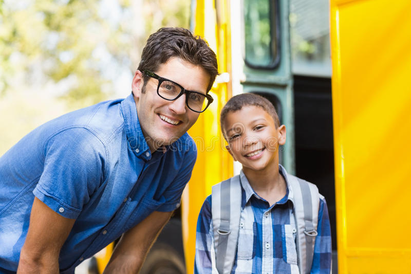 Smiling teacher and schoolboy standing in front of school bus stock images