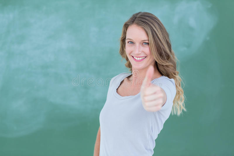 Smiling teacher standing thumbs up in front of blackboard. In classroom stock photos