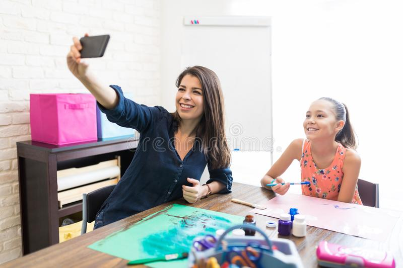 Smiling Teacher And Student Drawing While Talking Selfie At Home stock image