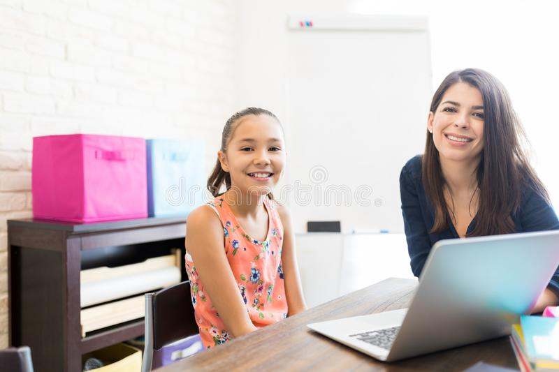 Smiling Teacher And Student With Laptop Sitting At Table royalty free stock images