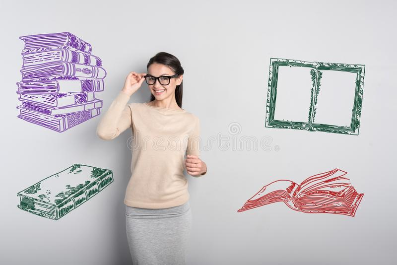 Smiling teacher touching her glasses and looking happy stock photos