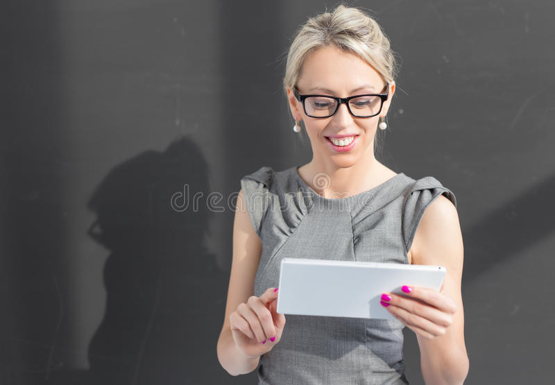 Smiling teacher using tablet computer stock photography