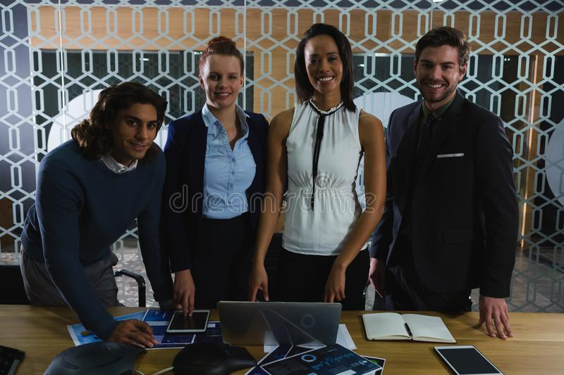 Smiling team of employees standing and smiling while looking into camera stock photos