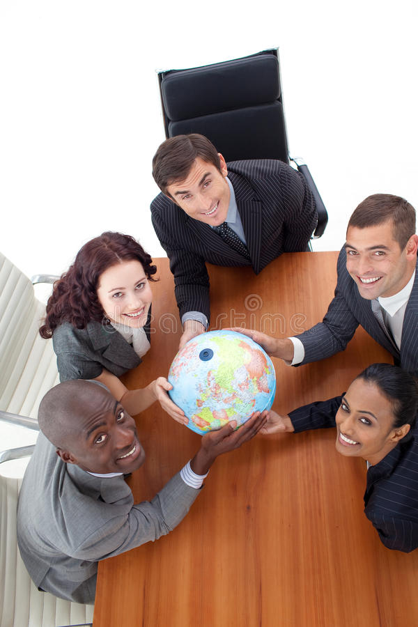 Smiling team holding a globe. stock image