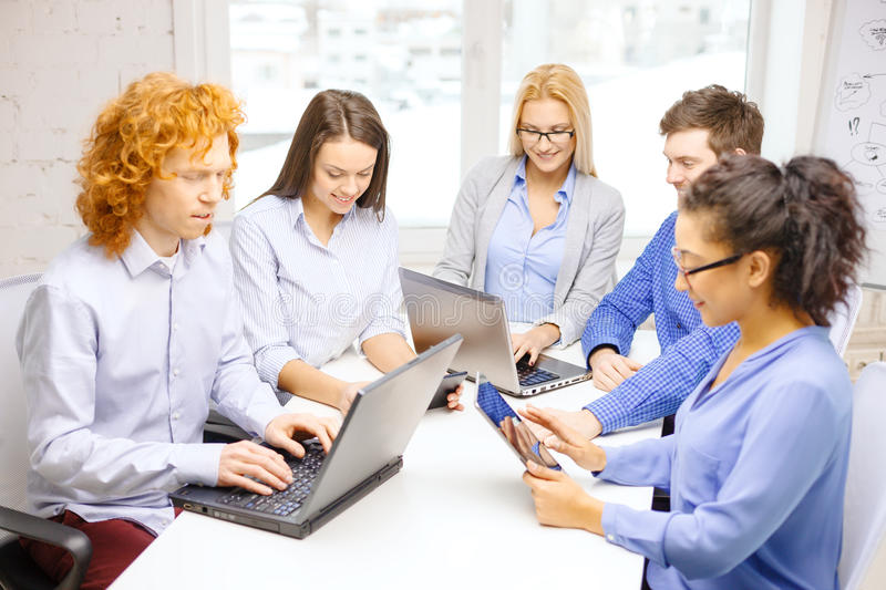 Smiling team with laptop and table pc computers. Business, office and startup concept - smiling creative team with table pc and laptop computers working in royalty free stock images
