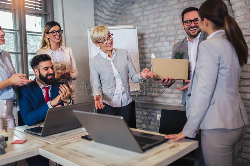 Smiling team leader executive introducing new just hired female employee to colleagues. In modern office stock image
