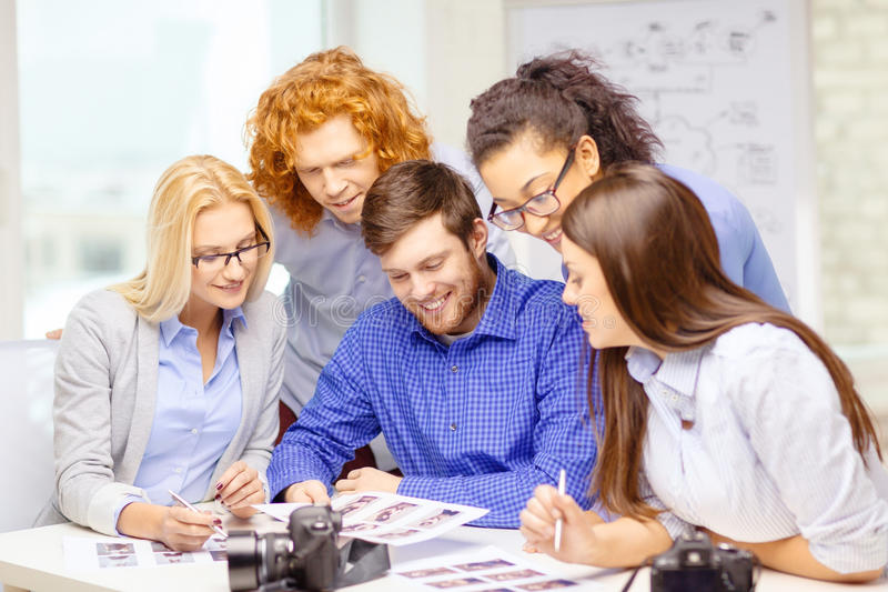 Smiling team with photocamera and images in office. Business, office and startup concept - smiling creative team with photocameras and images working in office royalty free stock photography