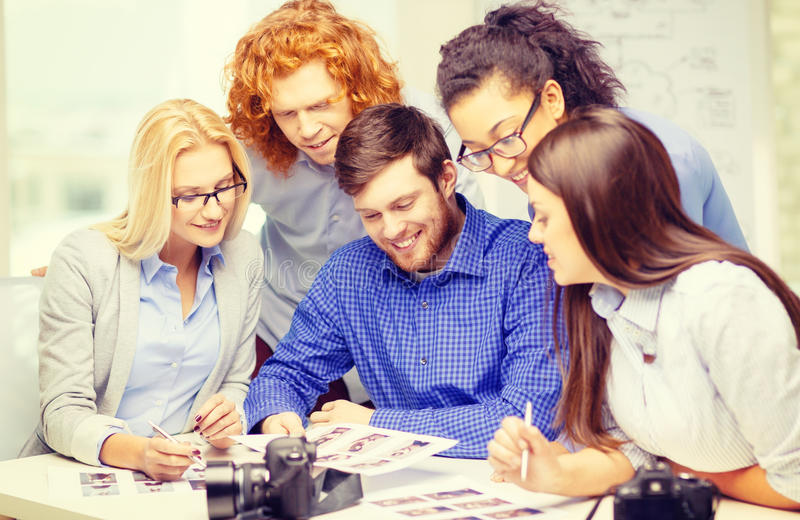 Smiling team with photocamera and images in office. Business, office and startup concept - smiling creative team with photocameras and images working in office stock image
