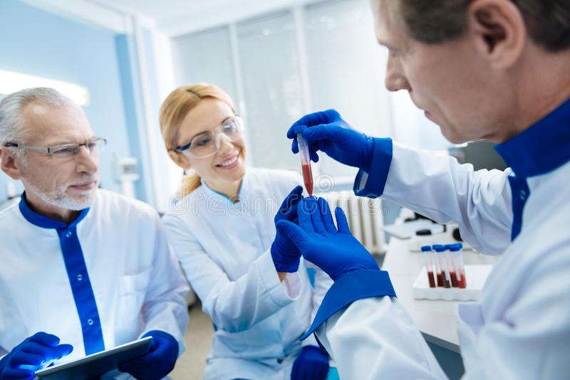 Smiling team of scientists conducting blood research stock images