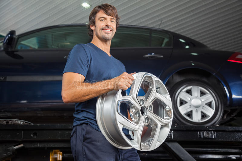 Smiling Technician Holding Alloy At Repair Shop. Low angle portrait of smiling technician holding metallic alloy at auto repair shop royalty free stock photo