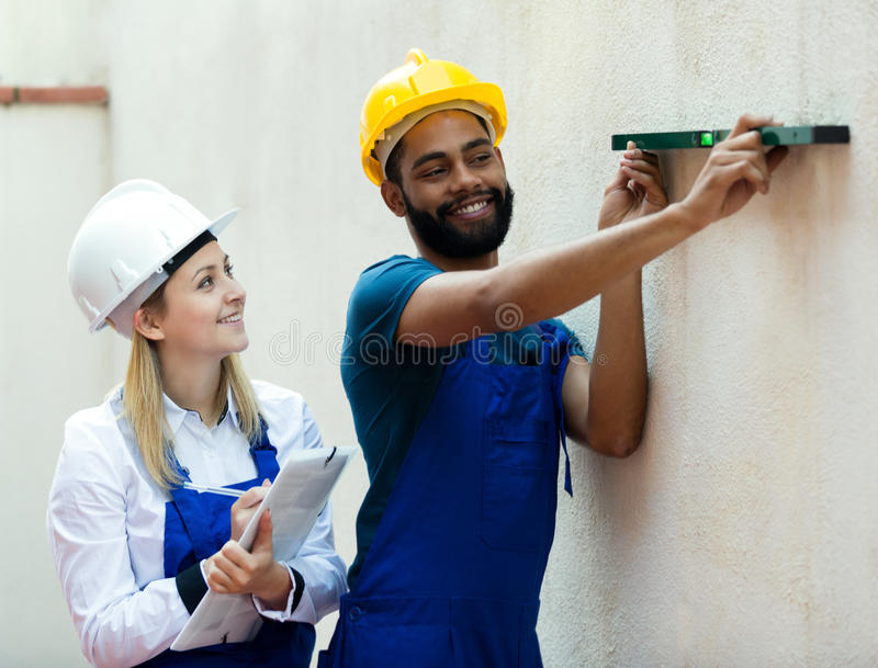 Smiling technicians smoothing the wall. Happy young technicians smoothing the wall surface at house stock images