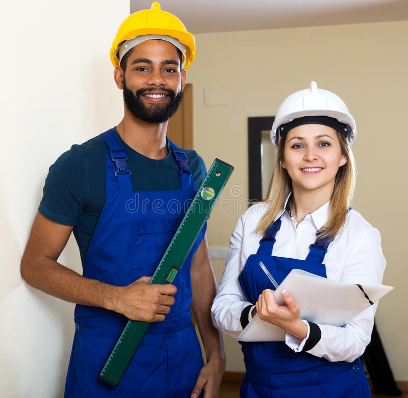 Smiling technicians smoothing the wall. Surface at house stock photo