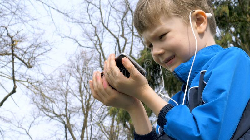 Smiling teen boy with smart phone listening or talking in british park. teenager and social media concept.  royalty free stock image