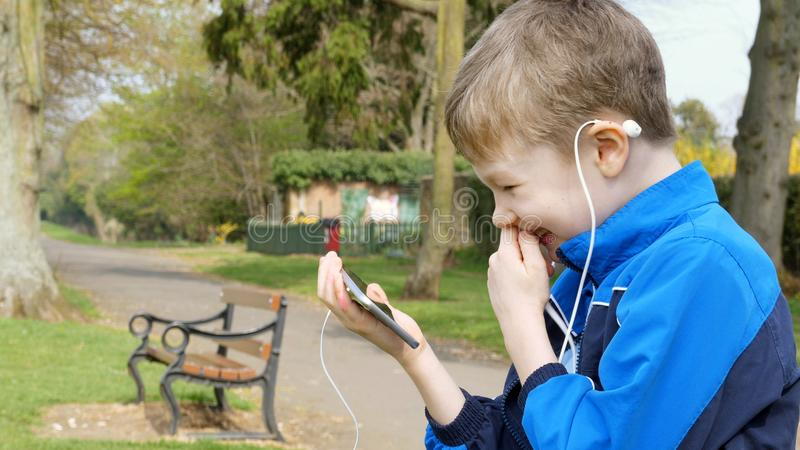 Smiling teen boy with smart phone listening or talking while sitting in british park. teenager and social media concept.  stock photography