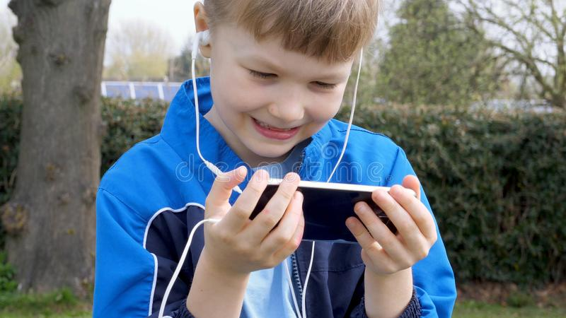 Smiling teen boy with smart phone listening or talking while sitting in british park. teenager and social media concept.  stock images