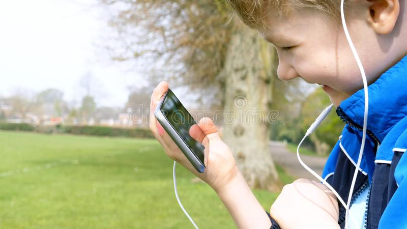 Smiling teen boy with smart phone listening or talking while sitting in british park. teenager and social media concept.  royalty free stock images
