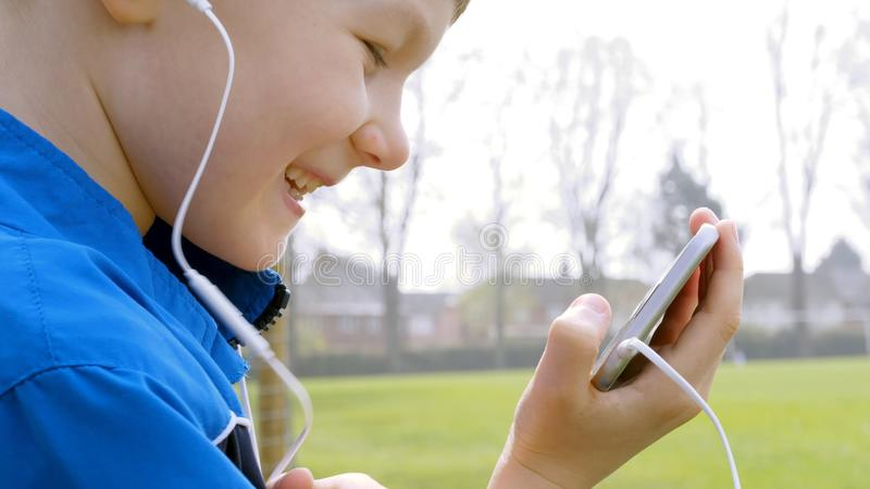 Smiling teen boy with smart phone listening or talking while sitting in british park. teenager and social media concept.  stock photo