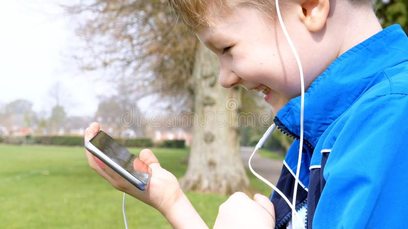 Smiling teen boy with smart phone listening or talking while sitting in british park. teenager and social media concept.  stock photos