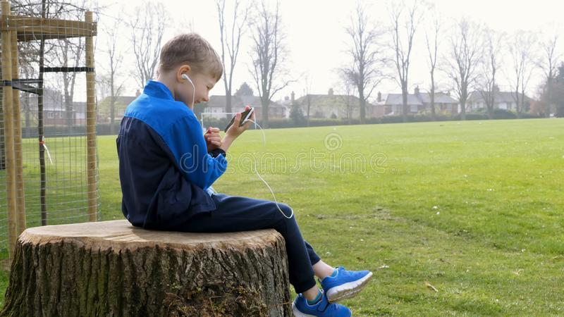 Smiling teen boy with smart phone listening or talking while sitting on stump in british park. teenager and social media. Concept stock image