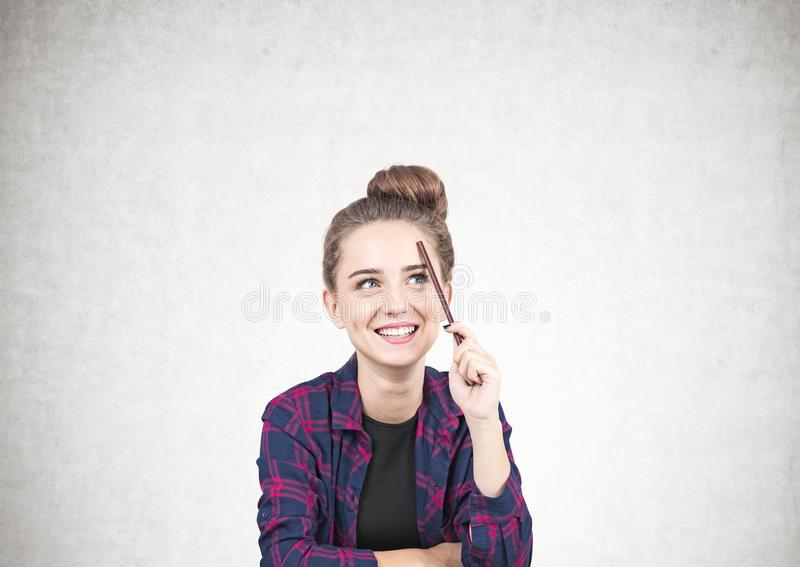 Smiling teen girl thinking, pencil, concrete stock photo