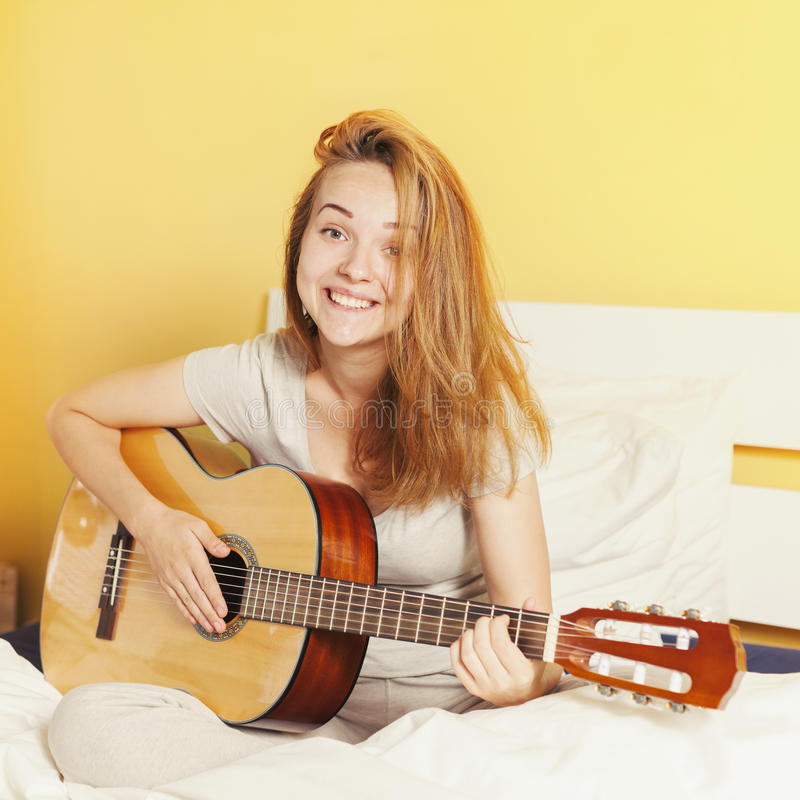 Smiling teen girl playing on guitar on the bed at home royalty free stock photos