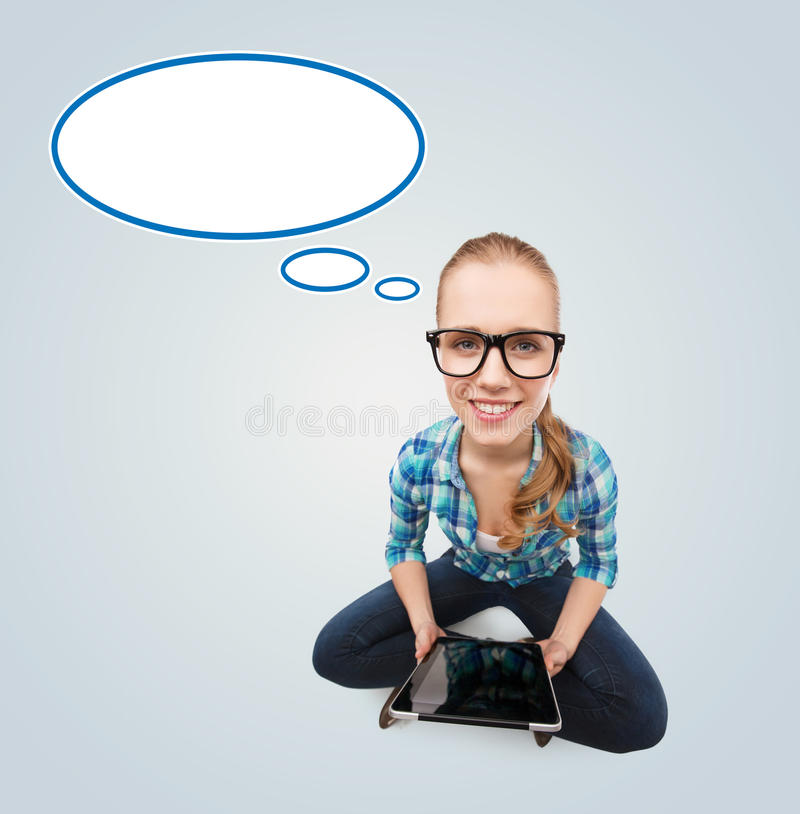 Smiling teen girl sitting on floor with tablet pc stock photography