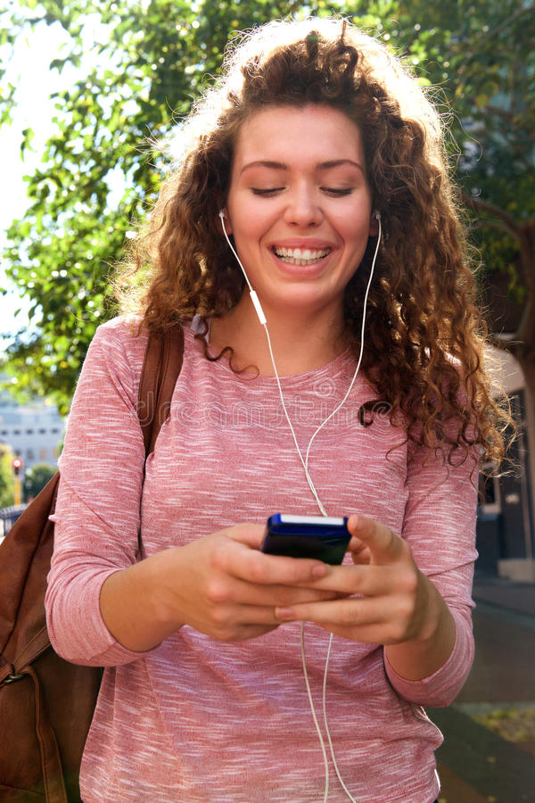 Smiling teen girl standing outside with mobile and earphones stock photo