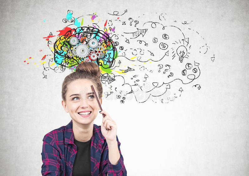 Smiling teen girl thinking, pencil, cog brain royalty free stock images