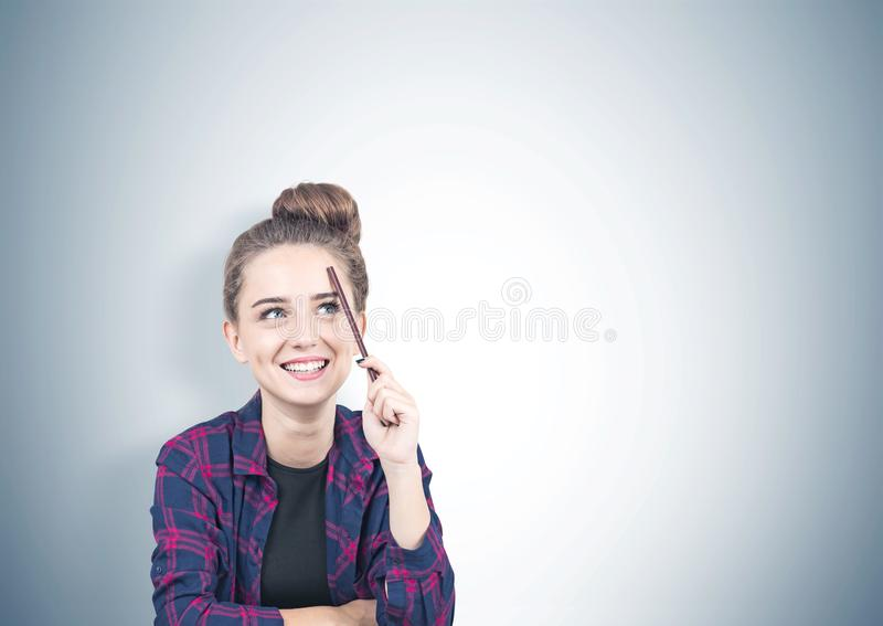 Smiling teen girl thinking, pencil, gray royalty free stock photography