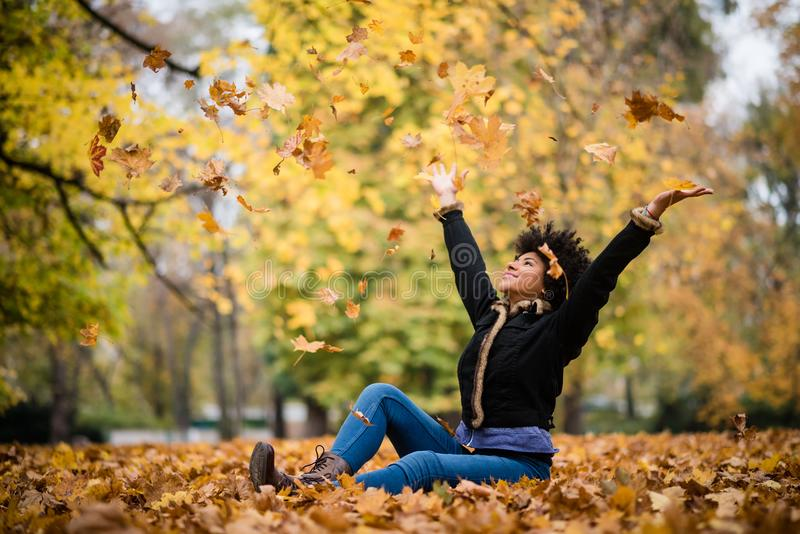 Smiling teen girl throwing leaves in the air royalty free stock image