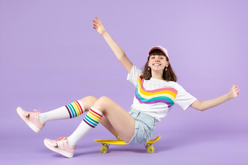 Smiling teen girl in vivid clothes sitting on yellow skateboard, spreading hands isolated on violet pastel wall stock image