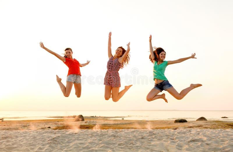 Smiling teen girls jumping on beach stock image