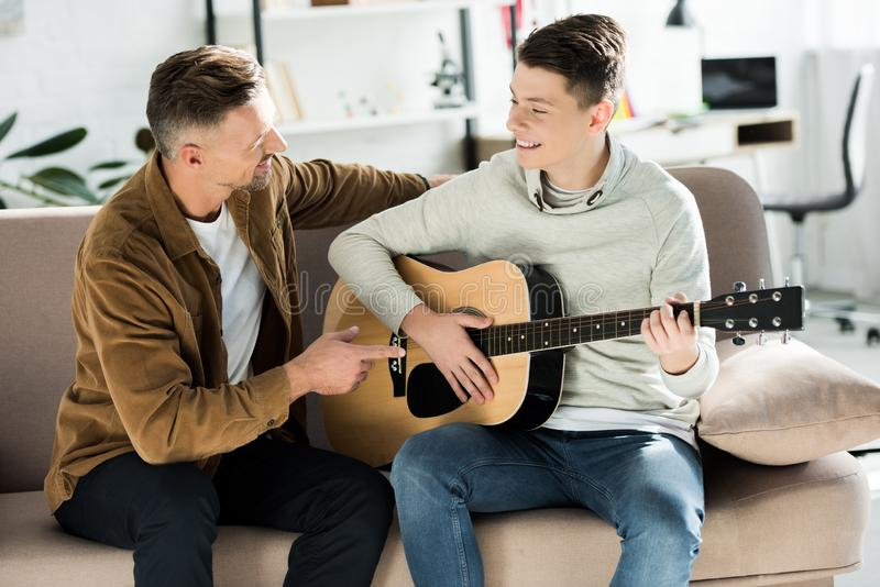 Smiling teen son playing acoustic guitar for father stock photo