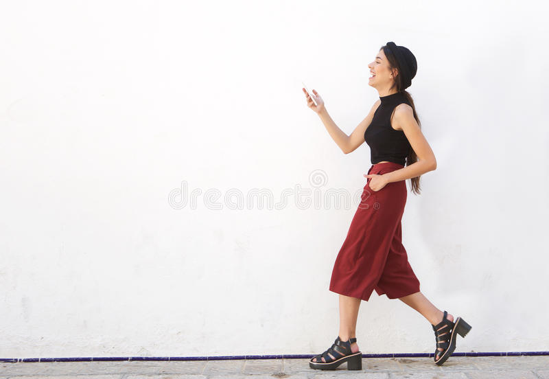 Smiling teen walking and looking at mobile phone stock photo